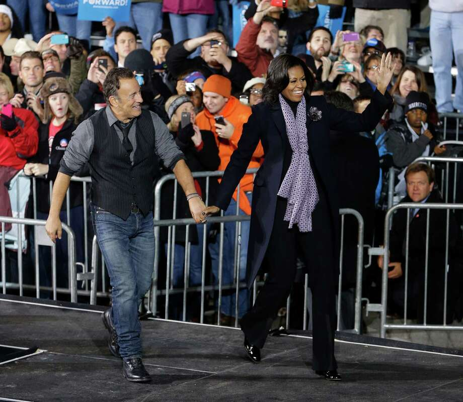 Singer Bruce Springsteen, left, walks with first lady Michelle Obama, right, on stage during the final 2012 campaign event for President Barack Obama in downtown Des Moines, Iowa, Monday, Nov. 5, 2012. (AP Photo/Pablo Martinez Monsivais) Photo: Pablo Martinez Monsivais, Associated Press / AP