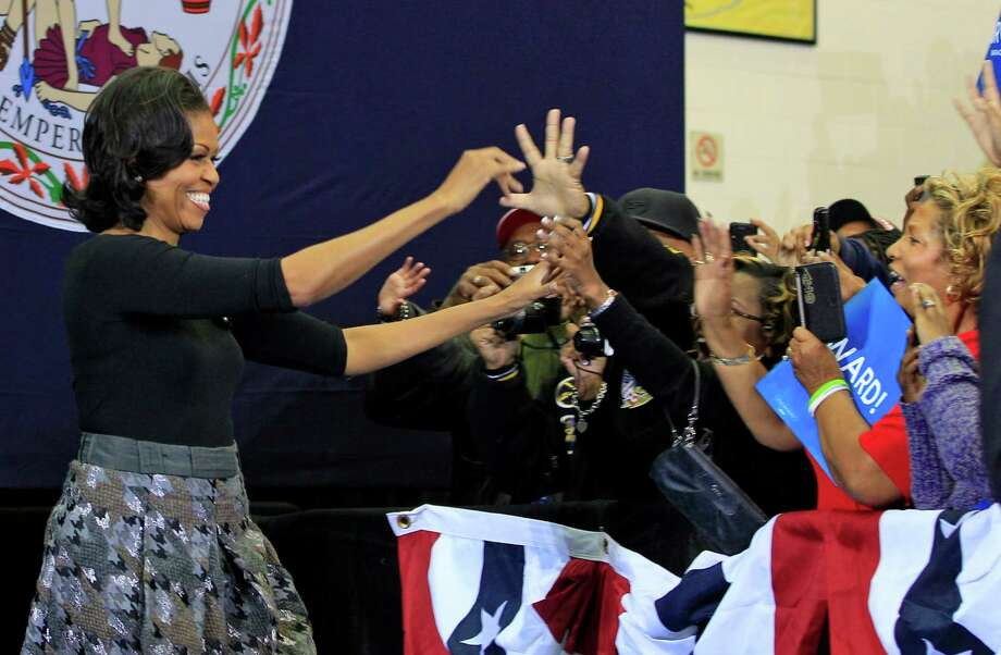 First lady Michelle Obama greets supporters as she arrives for a campaign rally for her husband, President Barack Obama, Friday, Nov. 2, 2012, at Virginia State University in  Petersburg, Va.  (AP Photo/Steve Helber) Photo: Steve Helber, Associated Press / AP