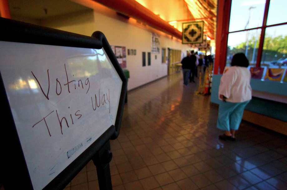 "Voters walk past a ""Vote This Way"" sign at the West Gray Recreation Center Tuesday, Nov. 6, 2012, in Houston. Photo: Cody Duty, Houston Chronicle / © 2012 Houston Chronicle"