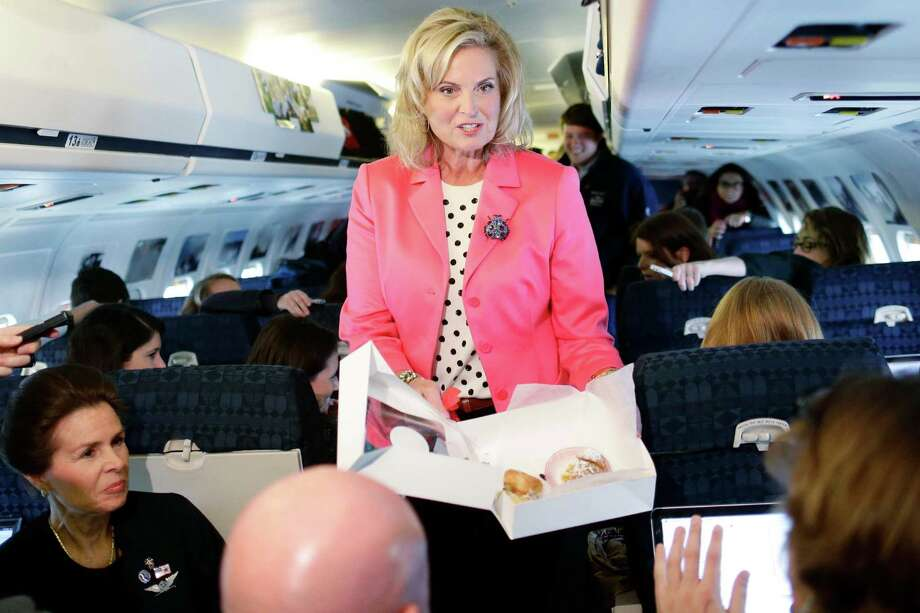 Ann Romney, wife of Republican presidential candidate and former Massachusetts Gov. Mitt Romney, hands out pastry to reporters on the plane after a campaign event at Portsmouth International Airport, in Newington, N.H., Saturday, Nov. 3, 2012. (AP Photo/Charles Dharapak) Photo: Charles Dharapak, Associated Press / AP