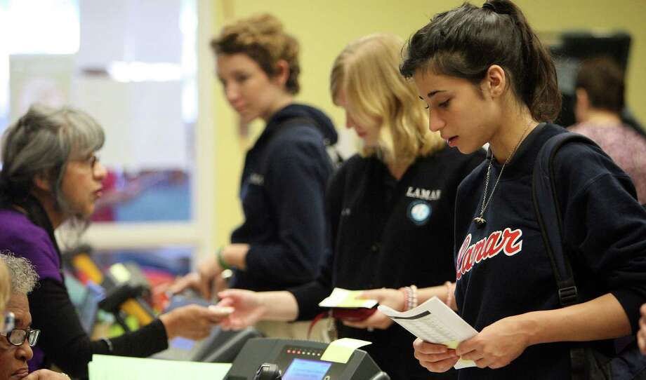 Lamer High School student Rebecca Altman right, checks in to vote along with fellow students Rachel Newsom 2nd from right and Rebecca Milton 3rd from right, at the Houston Metropolitan Multi-Service Center Thursday, Nov. 1, 2012, in Houston.    ( James Nielsen / Chronicle ) Photo: James Nielsen, Staff / © Houston Chronicle 2012