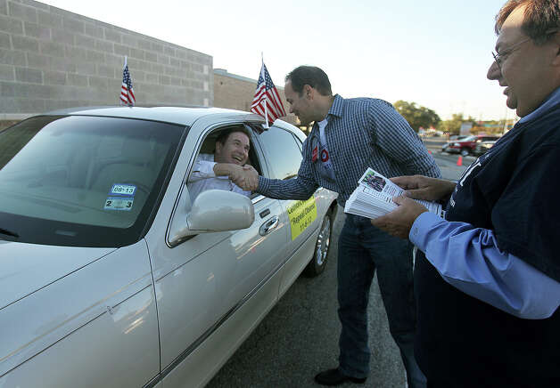 Tea Party member Matt Troy (in car) shakes hands with Tax Assessor Collector candidate Robert Stovall at Thousand Oaks Elementary School Election Day Tuesday November 6, 2012. On the right is Art Rossi who is running for judge in the 37th District Court. Photo: John Davenport/Express-News