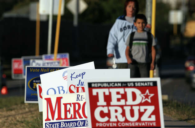 People walk past political signage election day Tuesday November 6, 2012 at Longs Creek Elementary School. Polls are open from 7:00 a.m. to 7:00 p.m. on Election Day. Photo: JOHN DAVENPORT, San Antonio Express-News / ©San Antonio Express-News/Photo Can Be Sold to the Public