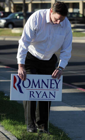 Matt Troy puts up a Mitt Romney sign in front of Thousand Oaks Elementary School Election Day Tuesday November 6, 2012. The polls close at 7:00 p.m. Photo: JOHN DAVENPORT, San Antonio Express-News / ©San Antonio Express-News/Photo Can Be Sold to the Public