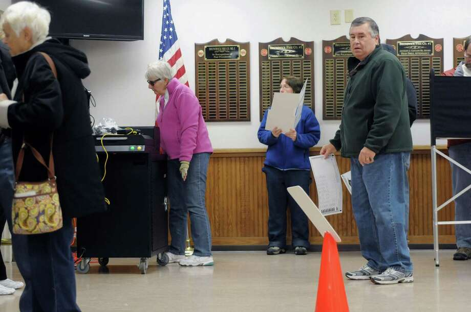 Voters wait in line with their ballots as other voters feed their ballots into the ballot reading machine at the Sycaway Fire House on Tuesday morning, Nov. 6, 2012 in Troy, NY.    (Paul Buckowski / Times Union) Photo: Paul Buckowski / 00019998A