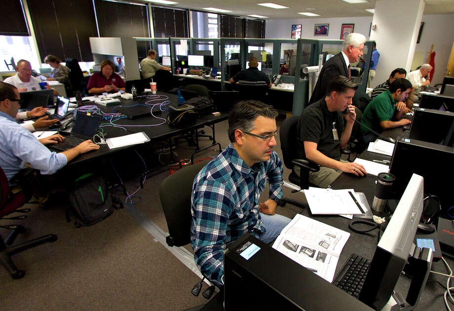 Harris County Information Systems technichian Christopher Rodriguez, center, works on his computer at the Harris County Administration building Tuesday, Nov. 6, 2012, in Houston. The techs provide support for polls around the county helping to set up the location including the machines and eslates, the machine that is used to vote. Photo: Cody Duty, Houston Chronicle / © 2012 Houston Chronicle