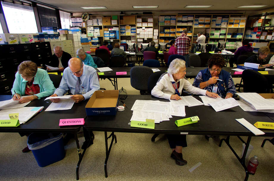 Harris County employees and volunteers go over mailed-in ballots at the Harris County Administration building Tuesday, Nov. 6, 2012, in Houston. The ballots are looked over where they are either deemed good meaning that they are ready to scan into the system, or put into a questions category where they are reviewed for different reasons. Photo: Cody Duty, Houston Chronicle / © 2012 Houston Chronicle