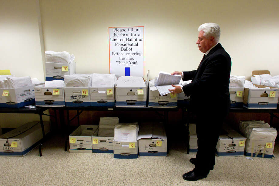 Harris County Clerk Stan Stanart looks over a poll book at the Harris County Administration building Tuesday, Nov. 6, 2012, in Houston. The wall of boxes include poll books containing a combined over 700,000 signatures from individuals who voted early. Photo: Cody Duty, Houston Chronicle / © 2012 Houston Chronicle