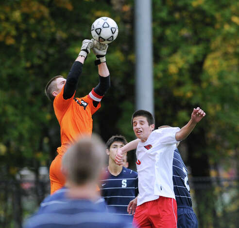 At left, Staples goalie James Hickok punches the ball out of the box as Joao Galbier # 6 of Greenwich approaches during the FCIAC boys soccer quarterfinal match between Staples high School and Greenwich High School at Greenwich, Friday afternoon, Oct. 26, 2012. Greenwich advanced with a 3-0 win. Photo: Bob Luckey / Greenwich Time