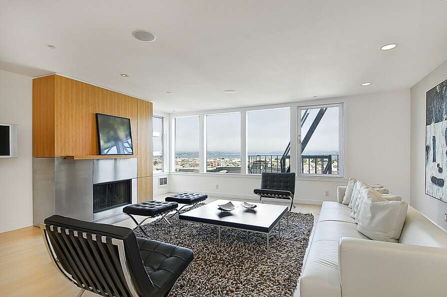 The living room offers a wood-burning fireplace and views of the city and San Francisco Bay.