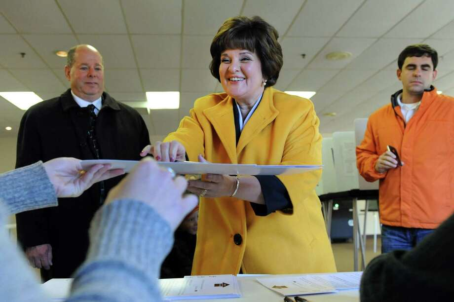 Kathy Marchione, running for the 43rd Senate seat, signs in to vote on Tuesday, Nov. 6, 2012, at the American Legion Post in Halfmoon, N.Y. Joining her are her husband, Frank, left, and son John Hickok. (Cindy Schultz / Times Union) Photo: Cindy Schultz / 00019991A