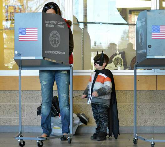 Dressed as Batman, 3-year-old Masom Reyell watches as his mother, Amber Reyell, casts her ballot Tuesday at Schalmont High School in Rotterdam.  (John Carl D'Annibale / Times Union) Photo: John Carl D'Annibale / 00019998A