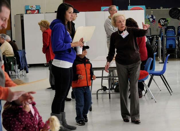 Poll worker Betty Fromm, rightr,directs  voters at the Broadview Middle School polling place in Danbury on Election day, Tuesday, Nov. 6, 2012. Photo: Carol Kaliff / The News-Times