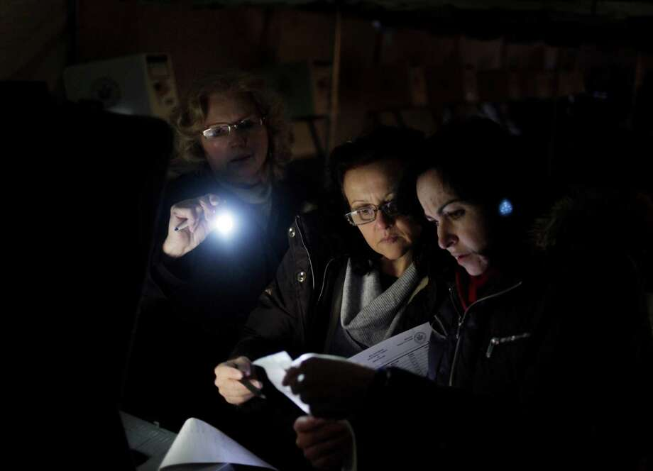 Poll workers Eva Prenga, right, Roxanne Blancero, center, and Carole Sevchuk try to start an optical scanner voting machine in the cold and dark at a polling station in a tent in the Midland Beach section of Staten Island, New York, Tuesday, Nov. 6, 2012. The original polling site, a school, was damaged by Superstorm Sandy. Photo: Seth Wenig, AP / AP