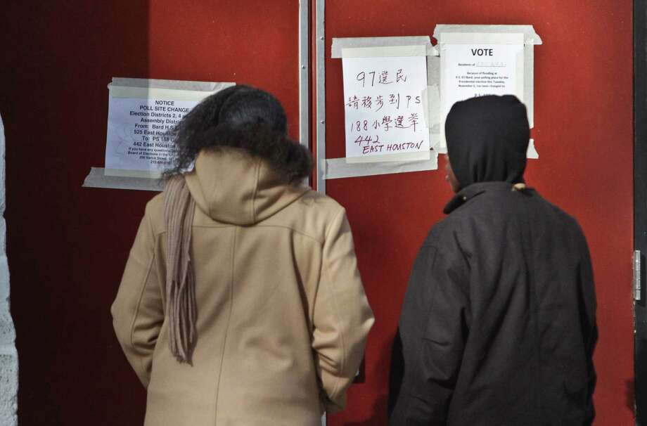 Voters arriving at a polling site read signs on a closed door about its relocation after flooding from Superstorm Sandy on Tuesday, Nov. 6, 2012 at Bard High School on Manhattan's Lower East Side, New York. Photo: Bebeto Matthews, AP / AP