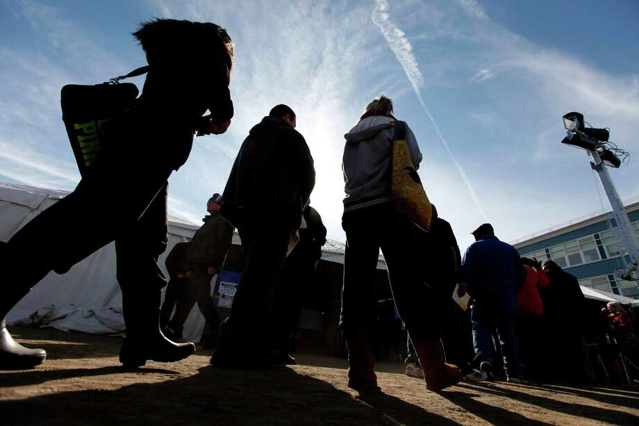 Voters wait in line to cast their ballots under a tent at a consolidated polling station for residents of the Rockaways on Election Day, Tuesday, Nov. 6, 2012, in the Queens borough of New York. Photo: Jason DeCrow, AP / FR103966 AP