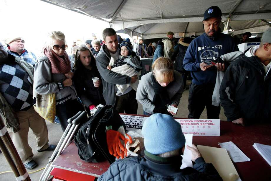 Voters check in before casting their ballots under a tent at a consolidated polling station for residents of the Rockaways on Election Day, Tuesday, Nov. 6, 2012, in the Queens borough of New York.  Voting in a the U.S. presidential election was the latest challenge for the hundreds of thousands of people in the New York-New Jersey area still affected by Superstorm Sandy, as they struggled to get to non-damaged polling places to cast their ballots in one of the tightest elections in recent history. Photo: Jason DeCrow, AP / FR103966 AP