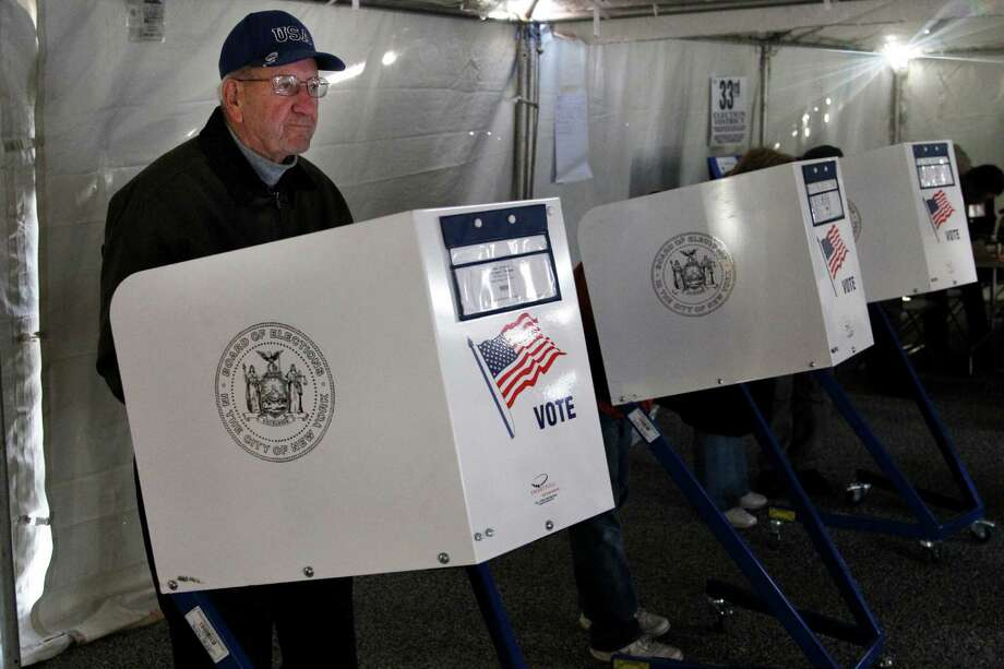 William Spade fills out his ballot at a polling site in a tent in the Midland Beach section of Staten Island, New York, Tuesday, Nov. 6, 2012. The original polling site, a school, was damaged by Superstorm Sandy. Voting in a the U.S. presidential election was the latest challenge for the hundreds of thousands of people in the New York-New Jersey area still affected by Superstorm Sandy, as they struggled to get to non-damaged polling places to cast their ballots in one of the tightest elections in recent history. Photo: Seth Wenig, AP / AP