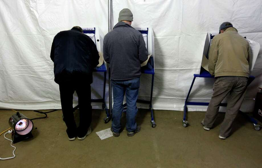 Voters fill out their ballots next to a space heater under a tent at a consolidated polling station for residents of the Rockaways on Election Day, Tuesday, Nov. 6, 2012, in the Queens borough of New York. Photo: Jason DeCrow, AP / FR103966 AP