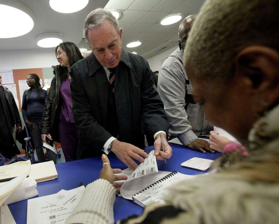 New York Mayor Michael Bloomberg helps a poll worker find his name in the registry before he votes in a school on New York's Upper East Side,  Tuesday, Nov. 6, 2012.  Gov. Andrew Cuomo signed an executive order Monday allowing residents to cast a so-called affidavit, or provisional ballot, at any polling place in the state for president and statewide office holders. Photo: Richard Drew, AP / AP