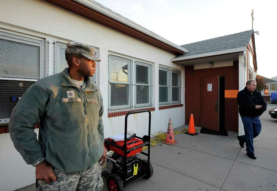 National guardsman Spc. Ian Suggs, of Jamaica, N.Y., stands at Bishop Molloy Recreational Center where voting takes place on Tuesday, Nov. 6, 2012, in Point Lookout , N.Y., one of several voting locations that were created as a result of Hurricane Sandy. Photo: Kathy Kmonicek, AP / FR170189 AP