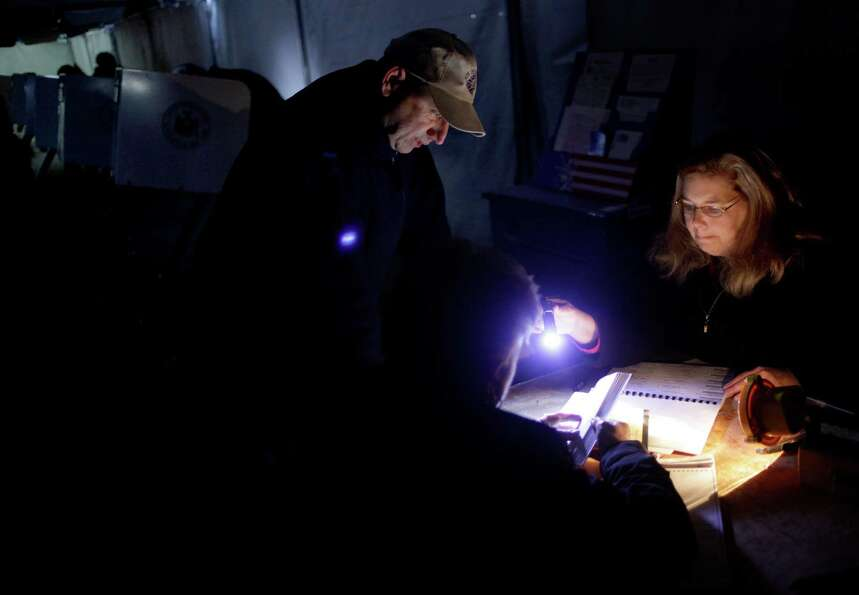 Poll worker Lisa Amico, right, helps voters by flashlight in a dark and unheated tent serving as a p