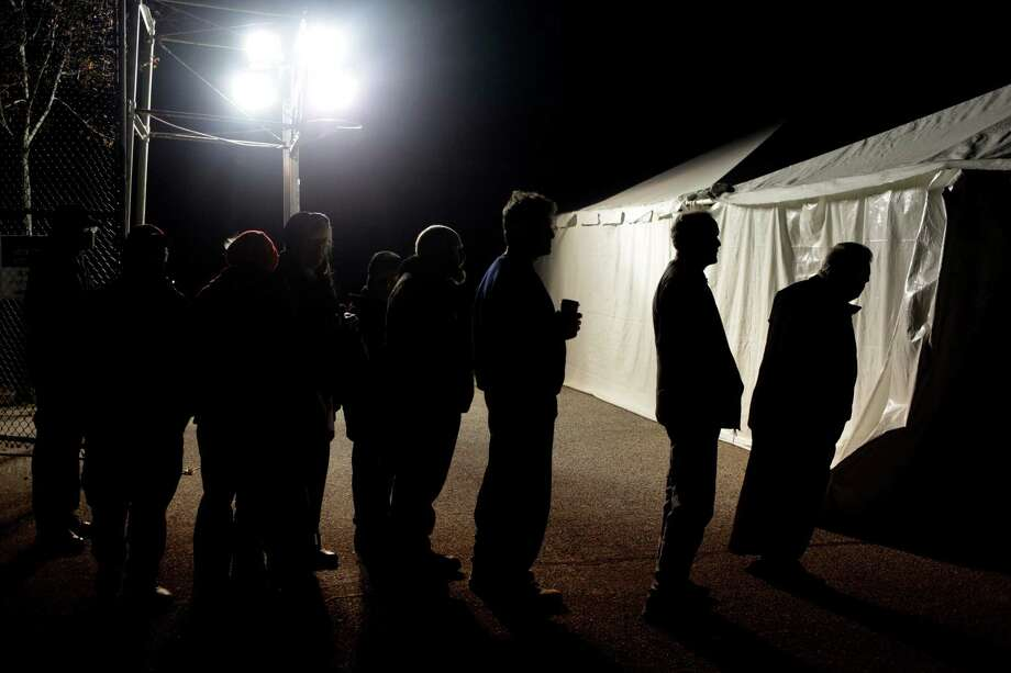 Under the lights of a generator, voters wait in line outside of a tent serving as a polling site in the Midland Beach section of Staten Island, New York, on Election Day Tuesday, Nov. 6, 2012. The original polling site, a school, was damaged by Superstorm Sandy. Photo: Seth Wenig, AP / AP