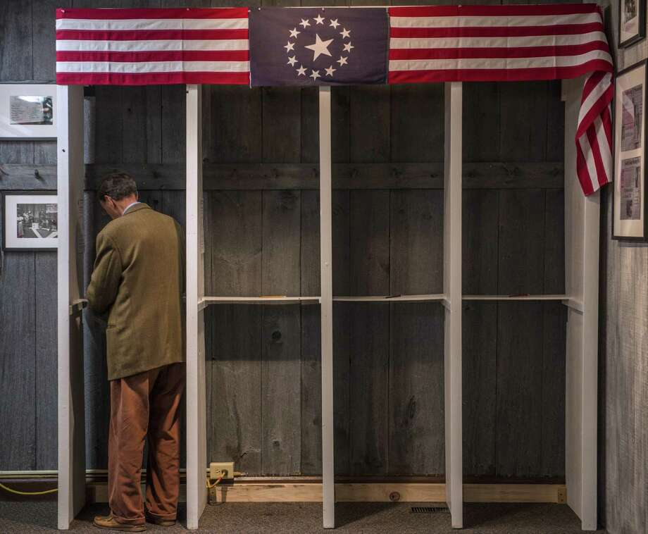 TOPSHOTS a man prepares to cast his ballot inside a polling booth just after midnight on November 6, 2012 in Dixville Notch, New hampshire, the very first voting to take place in the 2012 US presidential election.  The final national polls showed an effective tie, with either US President Barack Obama  or Republican challenger Mitt Romney favored by a single point in most surveys, reflecting the polarized politics of a deeply divided nation.  AFP PHOTO / ROGERIO BARBOSAROGERIO BARBOSA/AFP/Getty Images Photo: ROGERIO BARBOSA, AFP/Getty Images / AFP