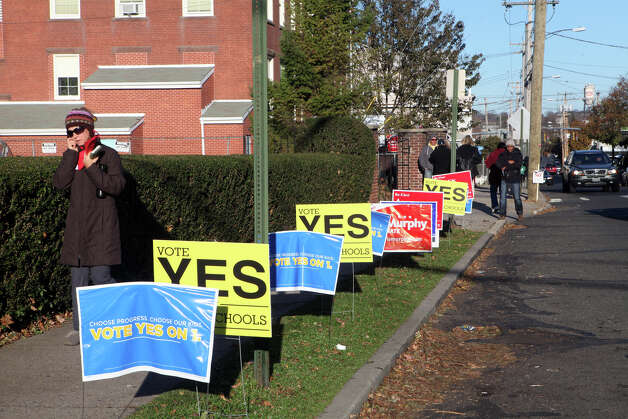 "Signs line the sidewalk of the Black Rock School polling location in Bridgeport on Tuesday, November 6, 2012. Many of the signs call for a ""yes"" vote on a charter-revision referendum that would give the mayor power to appoint the school board. Photo: Unknown, B.K. Angeletti / Connecticut Post freelance B.K. Angeletti"