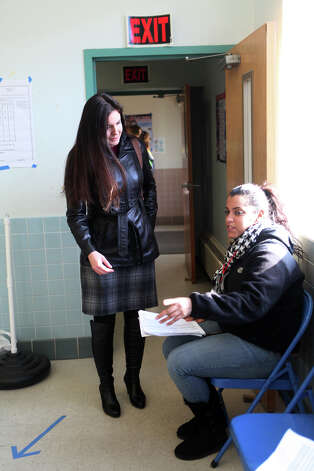 Distributer Nicole Cotto, right,  directs people to identification by address tables at Black Rock School polling location in Bridgeport on Tuesday, November 6, 2012. Photo: Unknown, B.K. Angeletti / Connecticut Post freelance B.K. Angeletti