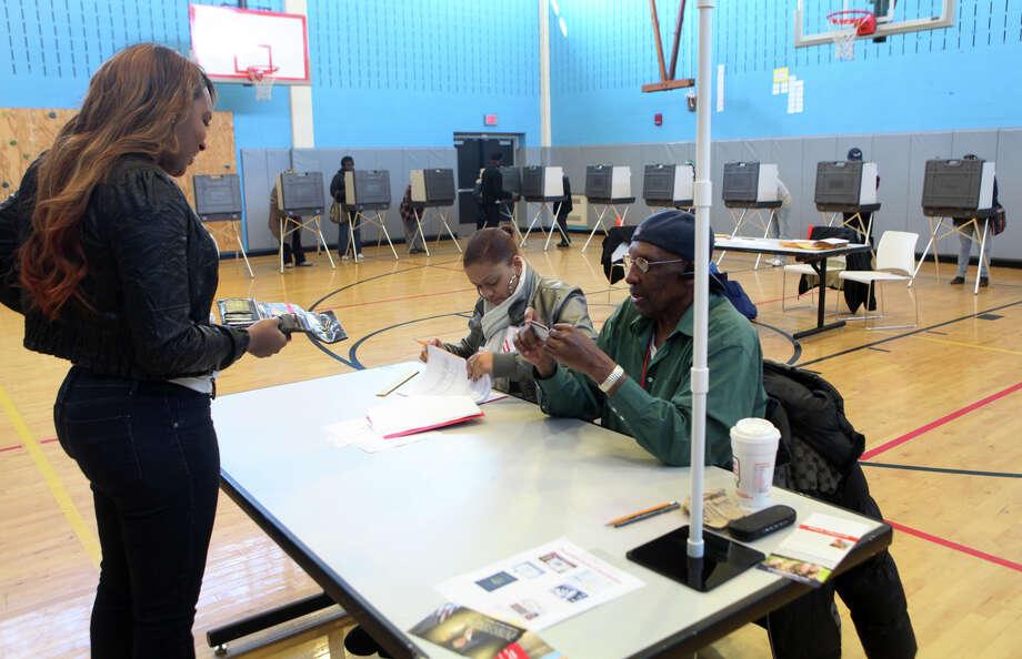 Aleah Byas, left, and Jesse Davis, right, check voter's identification at Geraldine Johnson School polling location in Bridgeport on Tuesday, November 6, 2012. Photo: Unknown, B.K. Angeletti / Connecticut Post freelance B.K. Angeletti