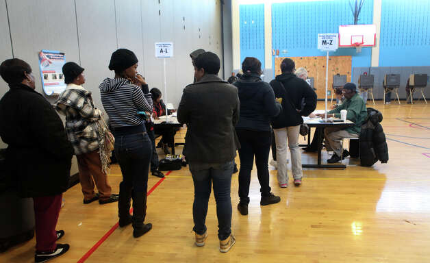 Voters wait to present identification at Geraldine Johnson School polling location in Bridgeport on Tuesday, November 6, 2012.  Voters lined up outside at 5:30am before polls opened. Photo: Unknown, B.K. Angeletti / Connecticut Post freelance B.K. Angeletti