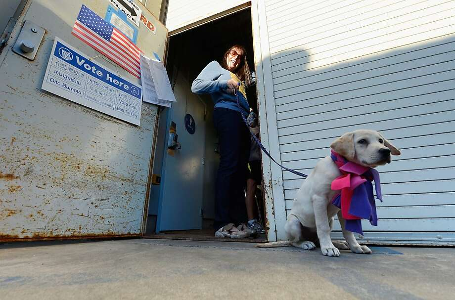 """Tracy Blumenthal, 39, waits in line with her dog Roxy to cast her ballot at a polling station in the garage of the Los Angeles County lifeguard headquarters on November 6, 2012 in Los Angeles, California. Californians will cast ballots in dozens of tight races including Gov. Jerry Brown's tax plan, abolishing the death penalty, easing the state's strict """"three strikes"""" sentencing law and also in the Presidential race between Democratic President Barack Obama and Republican candidate Mitt Romney. Photo: Kevork Djansezian, Getty Images"""