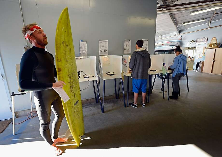 "Mike Wigart (left), 30, casts his ballot at a polling station in the garage of the Los Angeles County lifeguard headquarters on November 6, 2012 in Los Angeles, California. Californians will cast ballots in dozens of tight races including Gov. Jerry Brown's tax plan, abolishing the death penalty, easing the state's strict ""three strikes"" sentencing law and also in the Presidential race between Democratic President Barack Obama and Republican candidate Mitt Romney. Photo: Kevork Djansezian, Getty Images"