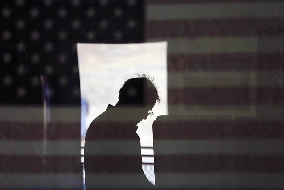 Hal Pigg casts his vote, reflected in an image of a flag, on Election Day Tuesday, Nov. 6, 2012, in Jamul, Calif. Photo: Gregory Bull, Associated Press