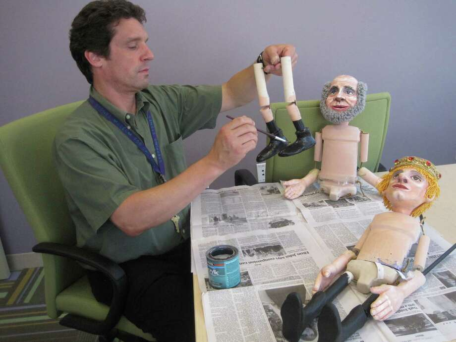 """Alan Louis, public programs manager at Stepping Stones Museum for Children in Norwalk, works on the characters in """"The Frog Prince and Other Tales."""" The puppetry spectacle will be performed Saturday, Nov. 10 through Friday, Nov. 16 and Wednesday, Dec. 12. Photo: Contributed Photo"""