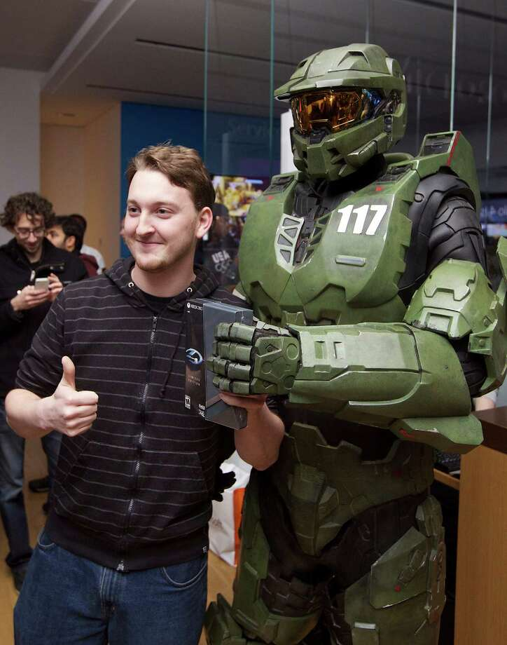 Fans lined up Monday night in Seattle to get their hands on Halo 4, the latest entry in the Xbox game franchise. Peter Gagnon of Seattle was first in line, getting the game just after midnight and a chance to pose with Halo character Master Chief. Photo: Invision For Xbox