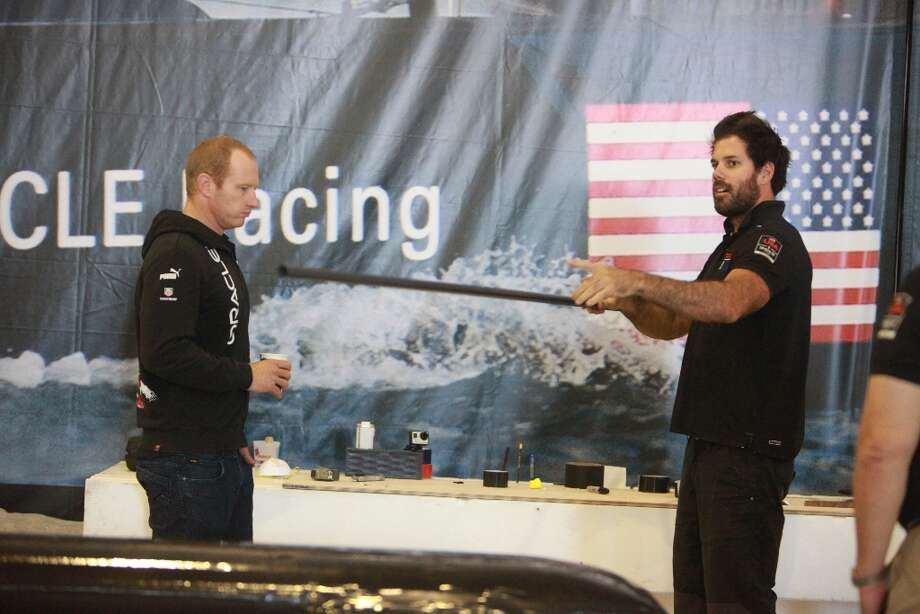 Shannon Falcone (right), Oracle Team USA sailing team member,  talks with Jimmy Spithill (left), Oracle Team USA skipper, as Falcone works on constructing a human-powered flying machine for Red Bull Flugtag San Francisco 2012 at the team base on Monday, November 5, 2012 in San Francisco, Calif. Part of a wing salvaged off the AC72 boat will be used on the flying machine being constructed. Photo: Lea Suzuki, The Chronicle / ONLINE_YES