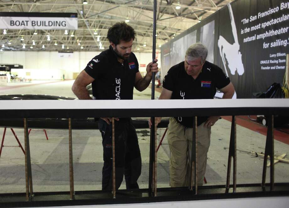 Shannon Falcone (l to r), Oracle Team USA sailing team member, and Tom Speer, Oracle Team USA Aero & Sail Project Leader, stand behind part of a wing salvaged from the Oracle Team USA AC72 boat, which capsized on October 16, 2012, as they discuss the construction of a flying machine for Red Bull Flugtag San Francisco 2012 at the team base on Monday, November 5, 2012 in San Francisco, Calif.  The part of the wing salvaged off the AC72 boat will be used on the flying machine being constructed. Photo: Lea Suzuki, The Chronicle / ONLINE_YES