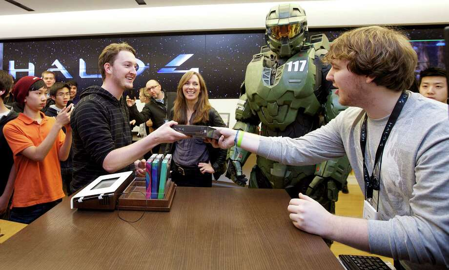 Peter Gagnon, left, of Seattle buys of the first copy of Halo 4 from Microsoft Store product advisor Jake Madle as Halo character Master Chief looks on at the game's launch, on Tuesday, Nov. 6, 2012 in Seattle. Photo: Invision For Xbox