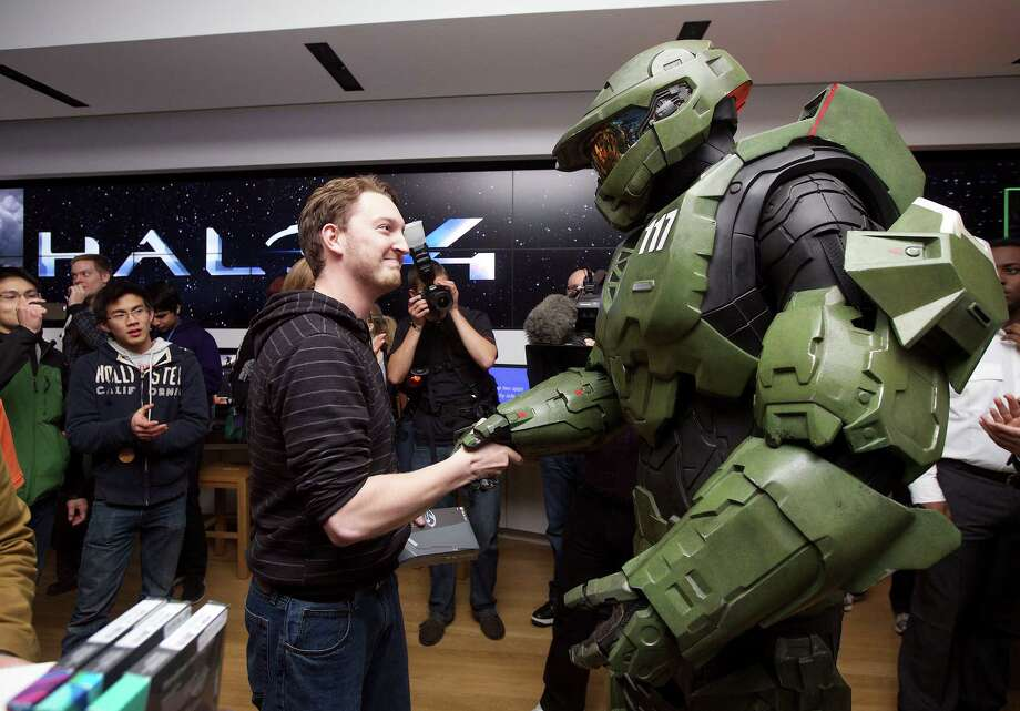 Peter Gagnon of Seattle shakes hands with Halo character Master Chief after buying the first copy of Halo 4 during the game's launch on Tuesday, Nov. 6, 2012 in Seattle. Photo: Invision For Xbox