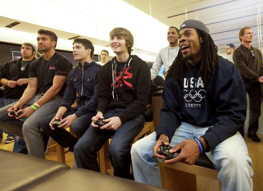 Seattle Seahawks defensive back Richard Sherman, far right, plays Halo 4 with other fans at a Microsoft store before the game's launch on Monday, Nov. 5, 2012 in Seattle. Photo: Invision For Xbox