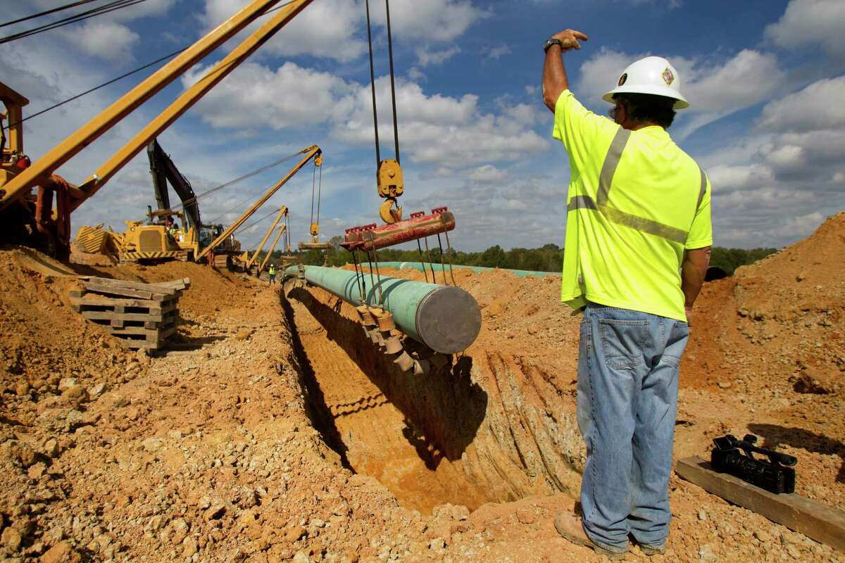 A crewmen directs a pipe for TransCanada's Keystone XL project as it's lowered into the ground in Wood County, Wednesday, Oct. 24, 2012, in Winnsboro.