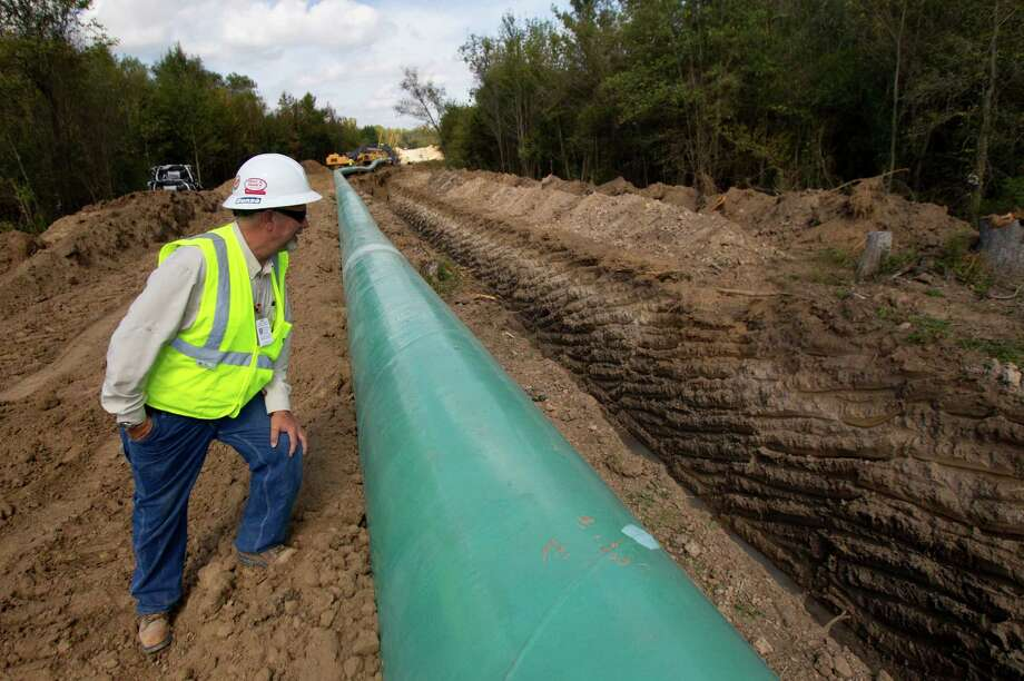 Wayne Knox, Assistant Construction Manager - Contractor for  TransCanada's Keystone XL project looks at a pipe before it's lowered into the ground in Wood County, Wednesday, Oct. 24, 2012, in Winnsboro. Photo: Cody Duty, Houston Chronicle / © 2012 Houston Chronicle