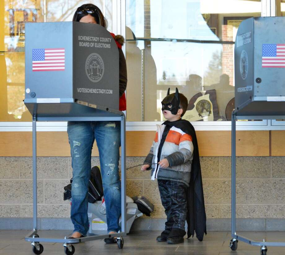 Dressed as Batman, 3-year-old Masom Reyell watches as his mother Amber Reyell casts her ballot at Schalmont High School in Rotterdam Tuesday Nov. 6, 2012.  (John Carl D'Annibale / Times Union) (Albany Times Union)