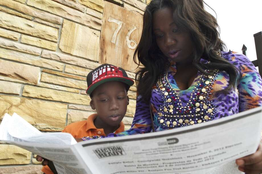 Shirletta Jones goes over a sample ballot with her son, Archie Cox, 7, as they wait in line to vote at Deliverance Tabernacle Church of the Nazarene in Miami, on Election Day, Nov. 6, 2012. (Maggie Steber/The New York Times) (NYT)