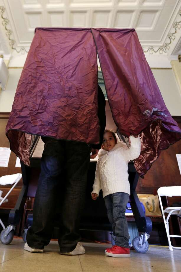 Madison Hasani, 3, peeks out of a voting booth while her father Alvaro Hasani, 28, casts his vote during Election Day at Hoboken City Hall, Tuesday, Nov. 6, 2012, in Hoboken, N.J. Residents were able to cast their votes in spite of most of the city still being in the dark following severe flooding caused by Superstorm Sandy. (AP Photo/Julio Cortez) (AP)
