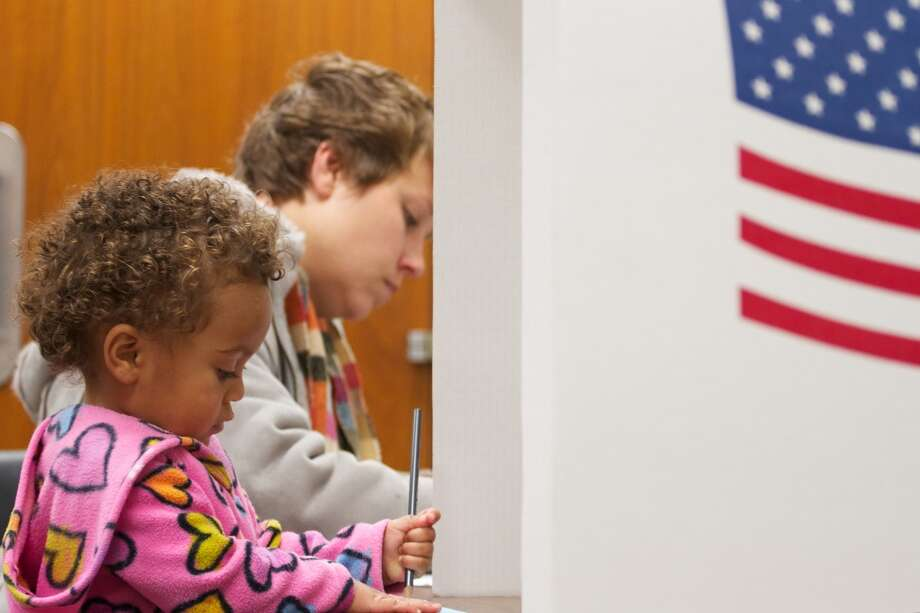 Lily Holthe, 2,  fills out a sample ballot while her mother casts her vote Tuesday, Nov. 6, 2012, at the Minnehaha County Administration Building in Sioux Falls, S.D. (AP Photo/Elijah Van Benschoten) (AP)