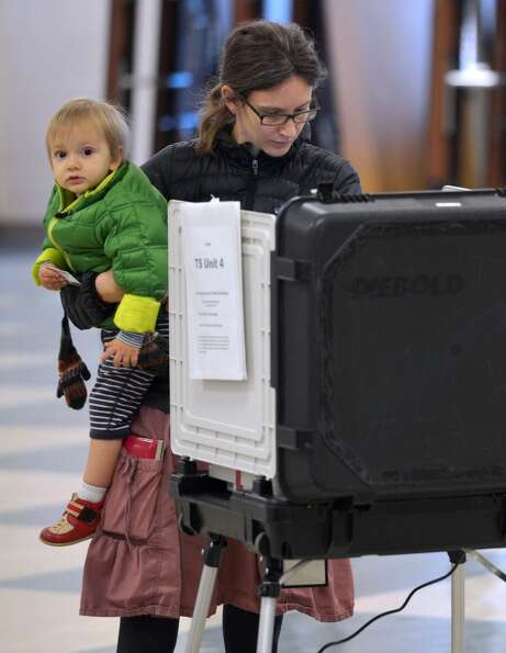 A woman holds a baby as she casts her ballot in a polling station at Wheaton High School on November