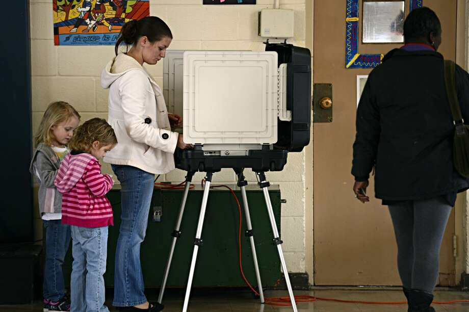 Ashley Zorman votes while her daughters Erica Zorman, left, and Keira Zorman, look on at Little Creek Elementary School in Norfolk, Va.  on Tuesday, Nov.  6, 2012. (AP Photo/The Virginian-Pilot, Amanda Lucier) (AP)